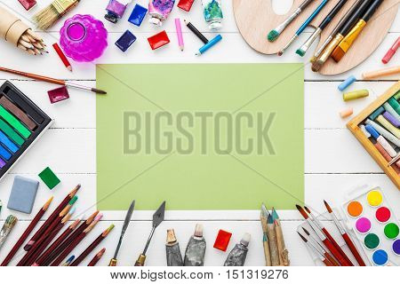 Watercolor Paints, Brushes For Painting, Pencils, Pastel Crayon And Green Paper Sheet On White Table
