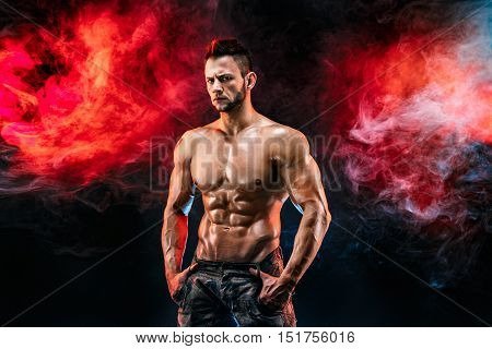 poster of Close up on perfect abs. Strong bodybuilder with six pack. Man with perfect abs, shoulders, biceps, triceps and chest, personal fitness trainer flexing his muscles in blue, red smoke