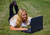 Teenager concentrates on laptop outdoors