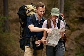 Hiking couple. Young people makes a hike in the woods. Active lifestyle, tourism. Tourist equipment. poster