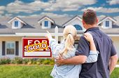 Young Adult Couple Facing and Pointing to Front of Sold Real Estate Sign and House. poster
