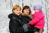 Grandmother, young mother and little daughter stand in woods in snow at winter