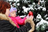 Young woman with small daughter stands near green tree with snow and touch red ball