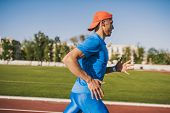 Horizontal Shot Determinated Young Caucasian Male Athletic Running Alone Along A Race Track In Stadi poster