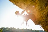 Image Of Man Climber In Helmet Clambering Up Cliff. Sunflare Effect. poster