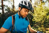 Outdoor Shot Of Handsome Young Professional Mountain Biker In Helmet And Blue Cycling T-shirt, Stand poster