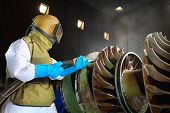 stock photo of sandblasting  - A worker working in a sandblast workshop - JPG