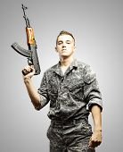 portrait of young soldier holding rifle wearing urban camouflage over grey background