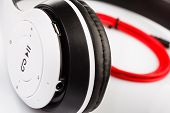White Wireless Headphones. Headphones On A White Background With A Red Cable. Close Up. poster