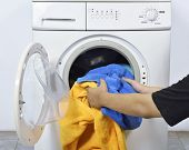 Man Loading The Dirty Towels Into Washing Machine For Washed In Home poster