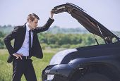 Worried Young Businessman Examining Broken Car Engine At Countryside.road Accident. Man Businessman  poster