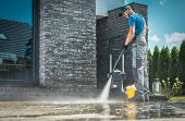 Pressure Washer Cleaning In Front Of The House. Caucasian Men In His 30s Washing Concrete Bricks Dri poster