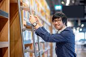 Young Asian Man Student Choosing Book From Bookshelf Using Ladder In Public Library, Male Researcher poster
