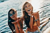 Sharing Fun With You. Top View Of Two Attractive Young Women In Swimwear Smiling And Blowing Confett poster