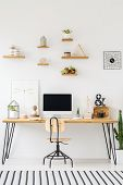 Wooden Shelves With Plants And Pots On A White Wall, Above An Industrial Desk With Modern Desktop Co poster