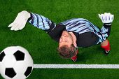 Overhead photo of a football goalkeeper missing saving the ball as it crosses over the line. Slight