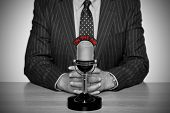 Photo of a news broadcaster sat at a desk and retro microphone with an On The Air illuminated sign,