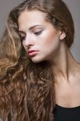 Closeup portrait of a beautiful young brunette woman with natural makeup, perfect skin and gorgeous curly hair