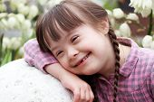 Portrait Of Smiling Girl On Flowers Background