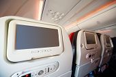 Screens for passengers in back of soft seats in modern airplane.