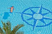 Woman has a rest on inflatable mattress in pool with wind rose image at bottom