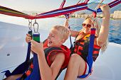 picture of parasailing  - Mother and her son sit in moving motorboat and ready to soar and paraglide - JPG