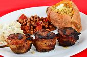 stock photo of mixture  - Upscale soul food dinner with skewered pork tenderloin wrapped in bacon and grilled to perfection with baked sweet potato and black eyed peas and macaroni salad - JPG