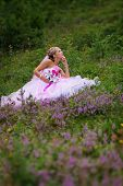 Young Beautiful Bride Sitting At A Forest Glade