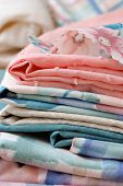 Stack of woven cotton fabrics in pastel colors for sewing project.  Macro with shallow dof.