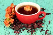 Herbal tea in cup, on color wooden background