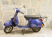 picture of vespa  - blue Motor Scooter Vespa with stone wall background - JPG