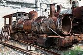 stock photo of locomotive  - old rusty steam locomotive in background of the wall - JPG