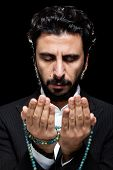 foto of tasbih  - Western Muslim Busiinessman Praying with Tasbih - JPG