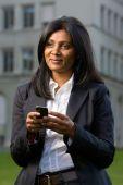 stock photo of handphone  - Pretty indian girl using mobile or handphone for communication - JPG