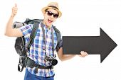 Tourist with backpack holding a big black arrow and giving thumb up isolated on white background