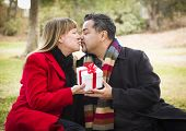 Young Attractive Mixed Race Couple Sharing Christmas or Valentines Day Gift in the Park.