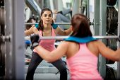 stock photo of squat  - Pretty Latin brunette doing some squats with a barbell and focusing on her routine - JPG