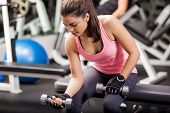 stock photo of bicep  - Gorgeous brunette lifting some weights and working on her biceps in a gym - JPG