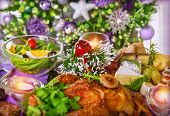 Close up photo of festive table setting, traditional Christmastime dinner with backed chicken on centerpiece of table, New Year eve concept