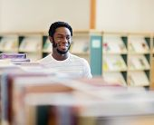 Happy African American male librarian looking away in bookstore