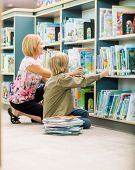 Mature teacher and boy selecting books from bookshelf in library