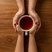 stock photo of ginger man  - Womans and mens hands holding hot cup of tea on wooden table - JPG