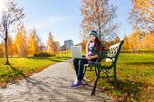 stock photo of 11 year old  - Beautiful school girl 11 years old sitting on the bench in park with laptop top on sunny autumn day wearing warm clothes