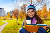 foto of 11 year old  - Close portrait of nice happy smiling 11 years old girl holding coffee mug and textbook wearing blue purple hat and scurf sitting on the bench in the park