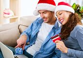Online Christmas Shopping. Happy Smiling Couple Using Credit Card to Internet Shop. Young Family with laptop and credit card buying online. Christmas and New Year Gifts. e-shopping