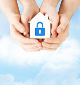 real estate and family home security concept - closeup picture of male and female hands holding whit