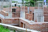 stock photo of reinforcing  - Red brick masonry and reinforced concrete pillars on house under construction - JPG