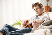 image of guitarists  - Young man playing guitar and composing a song sitting on sofa - JPG