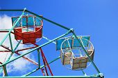 Part of colorful Ferris wheel with blue sky