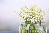 Beautiful lilies of the valley in glass vase on light background